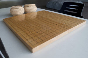Empty Go board with two basket of stone pieces